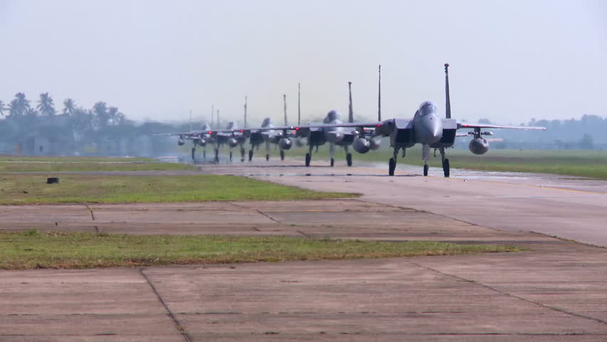 CIRCA 2010s - Numerous F-15 and F-16 fighter jets line up and taxi for takeoff in a military exercise.