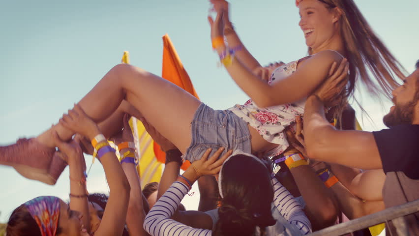 In high quality format happy hipster woman crowd surfing at a music festival