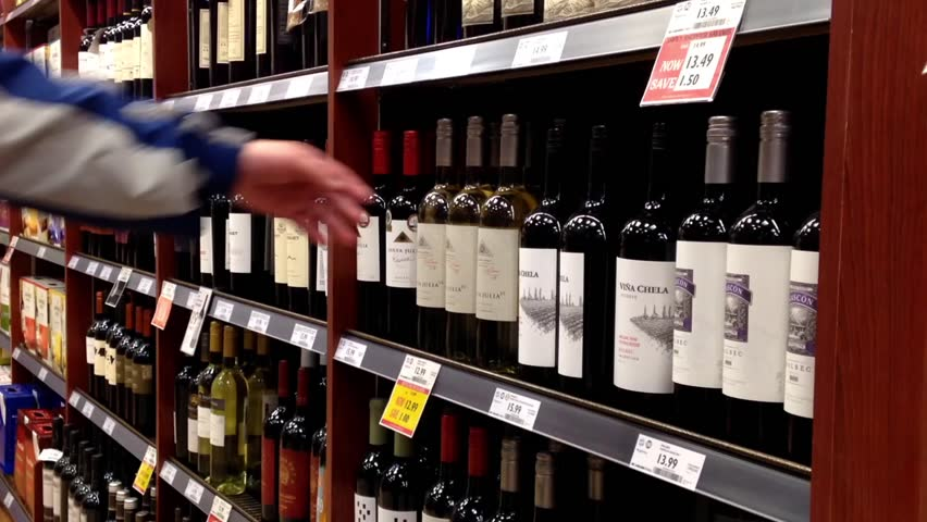 Coquitlam, BC, Canada - March 11, 2015 : A hand takes bottles of wine from the shelf.  Shopping and choosing a bottle of wine from the large selection to buy, grabbing it from the display rack. - HD stock footage clip
