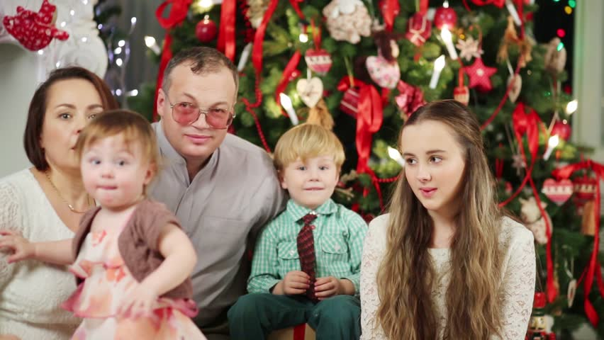 Happy family of five sits near Christmas tree and poses - HD stock footage clip