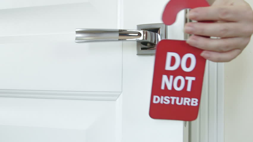 Guest hanging red sign do not disturb on the door of hotel room