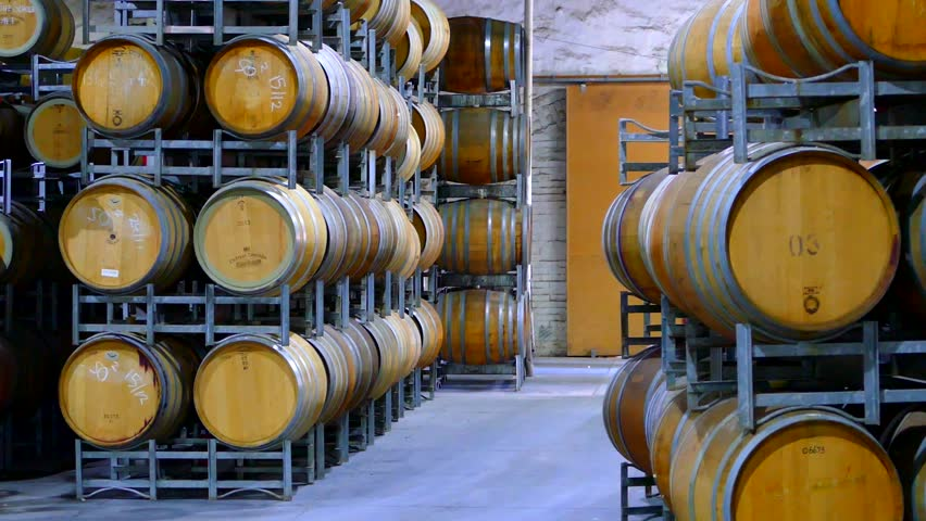 Video footage of fork lift loading and unloading wine barrels from truck to wine cellar. Featuring rows of oak barrels after vintage and harvest.