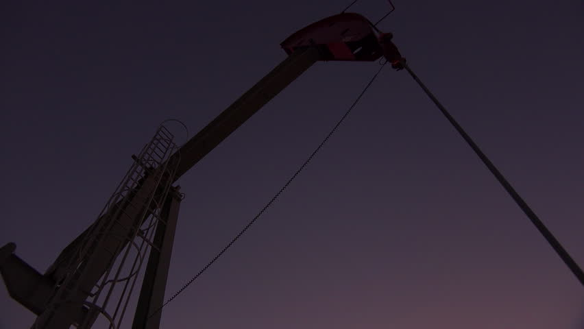 CALIFORNIA - CIRCA 2014 - Low of an oil derrick pumping against the night sky. - 4K stock video clip