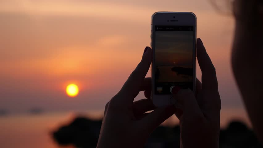 Woman Taking Pictures with her Smartphone at Sunset on the Beach near the Sea on Vacation. Slow Motion. HD, 1920x1080.