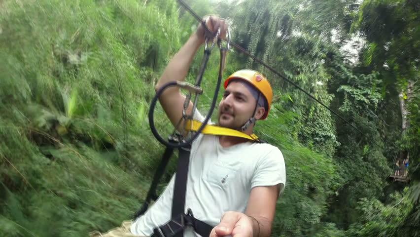 Young man on ZIP-LINE. Young man enjoying on zipline attraction.