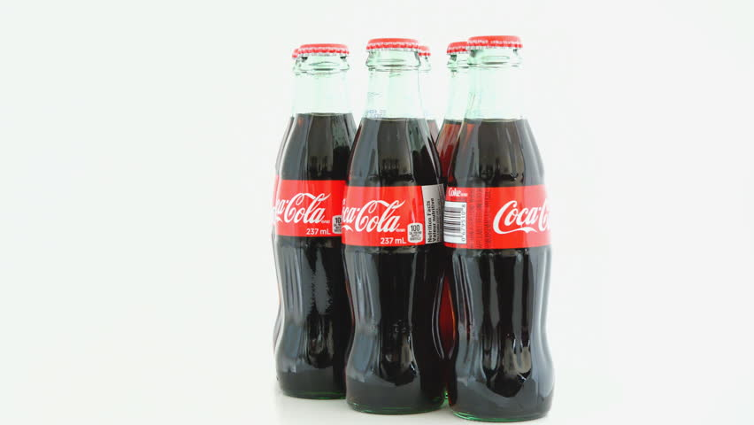 TORONTO,CANADA-MARCH 18,2015:Coca Cola bottles turning over white background stock footage clip.Coca-Cola is carbonated soft drink sold in stores, restaurants, and vending machines all over the world
