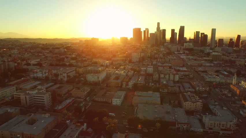 Los Angeles Aerial Downtown Cityscape Sunrise v88 Low flying turning aerial revealing downtown cityscape at sunrise.