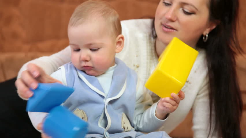 Mother with baby boy playing colored blocks on floor in the room - HD stock footage clip