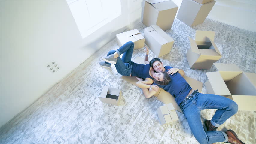 Moving, repairs, new home. Couple girl and guy lie on the floor in an embrace while man and woman lying on the floor among the boxes in an empty apartment
