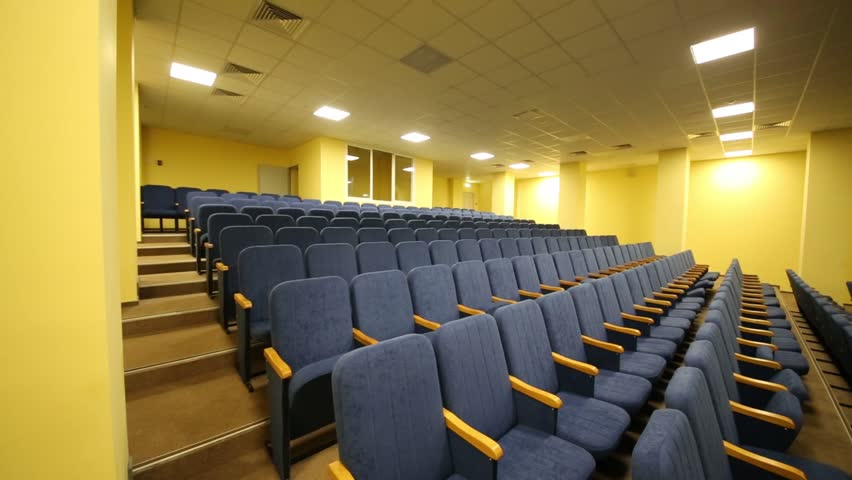 Simple and small auditorium with blue armchairs and yellow walls | Shutterstock HD Video #9307574