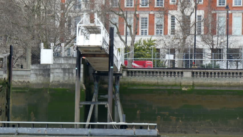 A white small bridge-like structure in Thames river. Could be an unfinished project in London in 4K - 4K stock footage clip