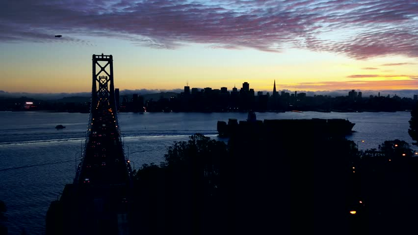 Treasure Island, California - October, 2014 - Real time 4K footage of the San Francisco Bay Bridge and skyline silhouette at sunset.