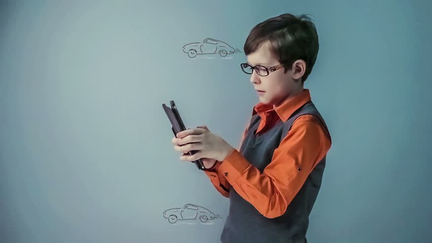 Teenager boy with glasses plays the game  the race cars go on the tablet video hd 1920x1080 | Shutterstock HD Video #9386333
