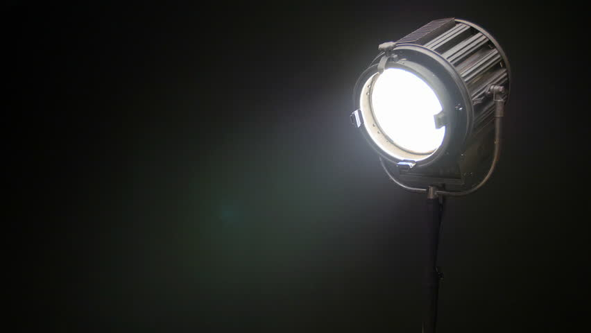 Vintage Theater Stage Spotlight with Fresnel Lens Slowly Turn On and Off in Front of Black Background, Producing a Lens Flare. - HD stock video clip