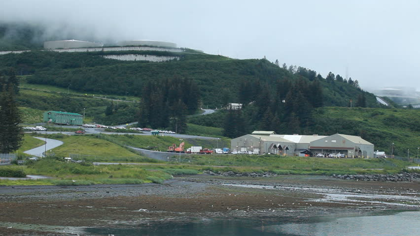 Valdez oil pipeline terminal building and storage tanks. Loading dock area where ships are filled for transport of crude oil. Misty fog weather. Mist and beautiful clouds. - HD stock video clip