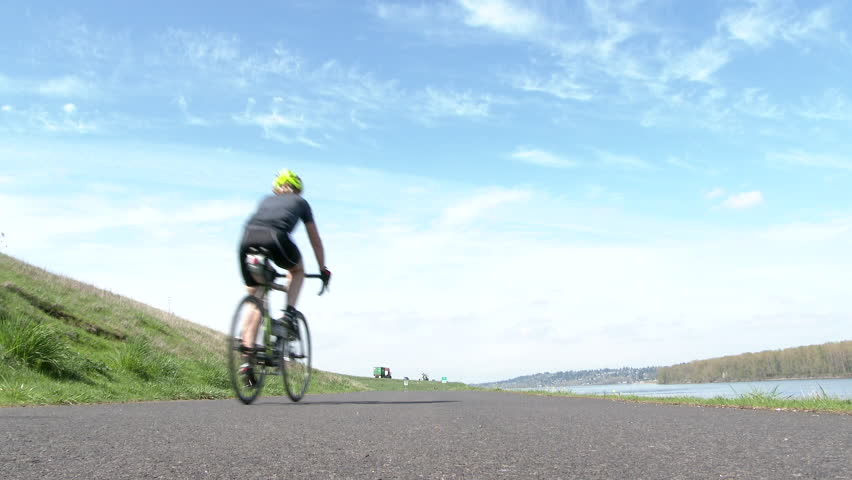 Unrecognizable cyclist riding by on bike path with cars and airplane passing by.