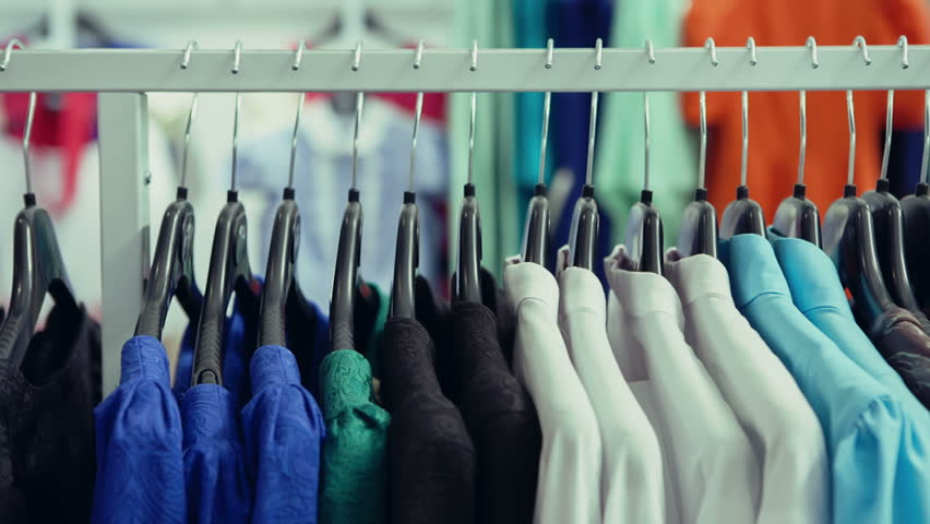 DOLLY MOTION: Variety of clothes hanging on rack in boutique
