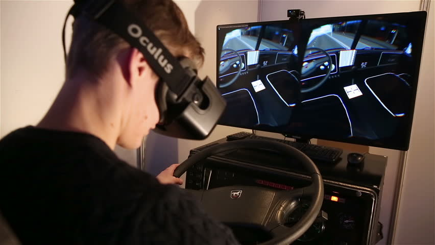 MOSCOW, RUSSIA - MARCH 29, 2015: A young man uses a car simulator using virtual reality technology. Exhibition of modern technologies TechTrends Expo.