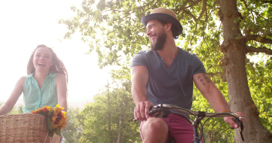 Young couple cycling happily together through a sunny park on street in summertime | Shutterstock HD Video #9426302