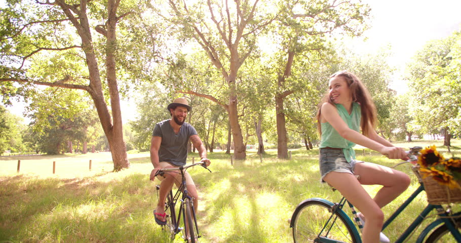 Happy young hipster couple cycling in summer together in a park in Slow Motion, Panning