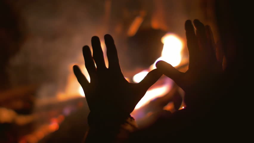 The man warm hands outdoor by the flame background. Heat and powerful flame. Real time capture. Shot with Red Cinema Camera - 4K stock video clip