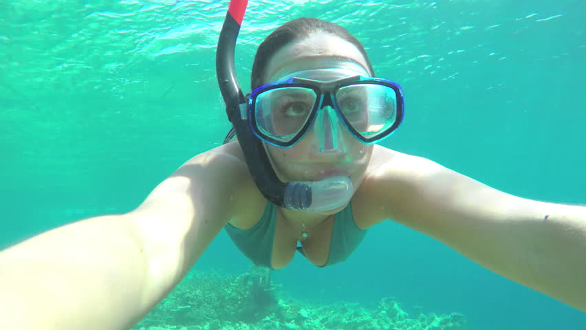 UNDERWATER SELFIE: Young woman snorkeling the coral reef