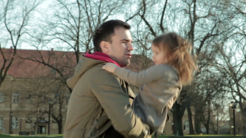 Young father holding and turning little daughter. Man with beautiful female child standing in park, laughing and playing with her. Dad and female kid enjoying in sunny day. Happy childhood, parenthood - HD stock video clip