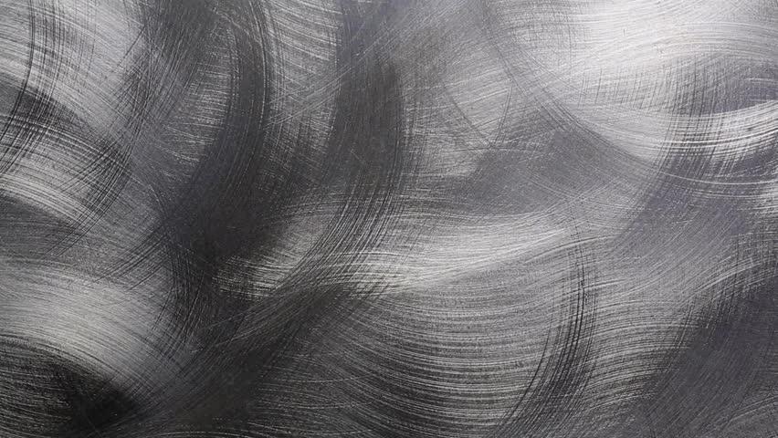 camera sliding above a sheet of circular brushed metal