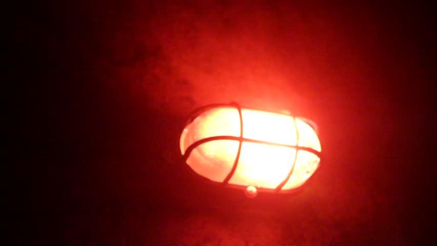 Blinking red alarm lamp in a dark room.