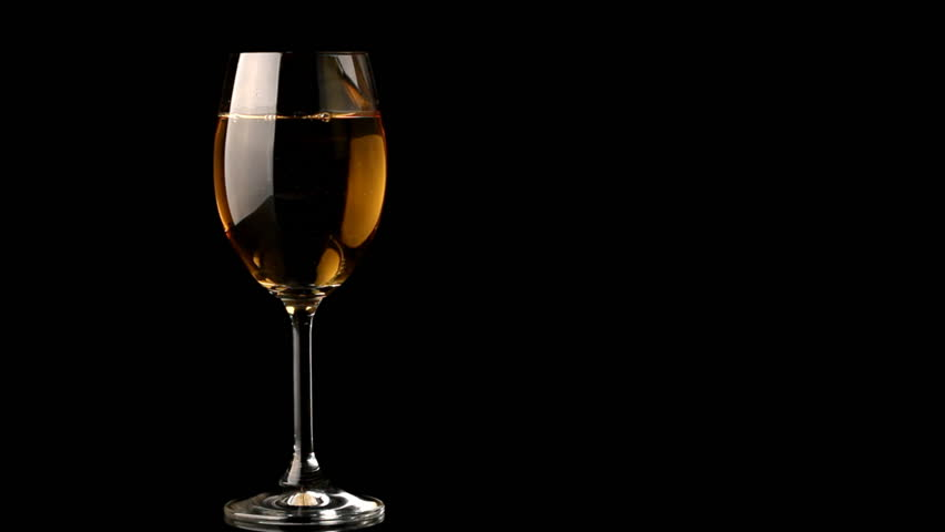 Pouring White Wine Into A Glass On Black Background Stock
