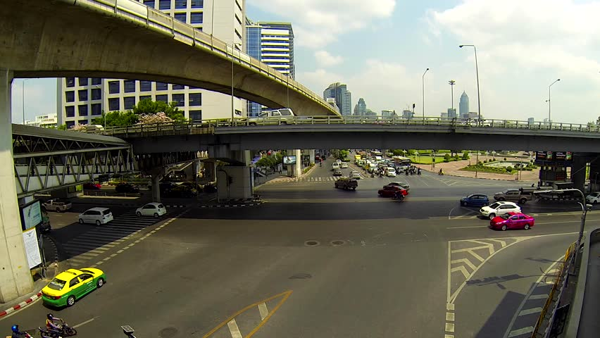 BANGKOK - March 2015: Bangkok's traffic with BTS sky trains passing by. Silom intersection. Speed up - HD stock video clip