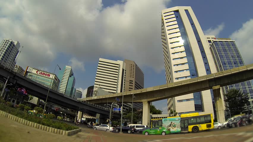 BANGKOK - March 2015: Bangkok's traffic with BTS sky trains passing by. Silom - HD stock video clip