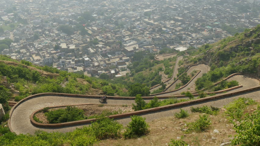 JAIPUR, INDIA - 21 OCTOBER 2014: A motorbike takes a winding road up from the city of Jaipur. - 4K stock footage clip