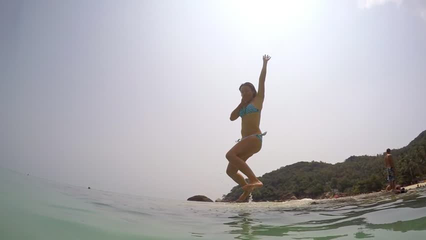 Young Woman Jumping and Diving into Sea. Slow Motion. HD, 1920x1080.