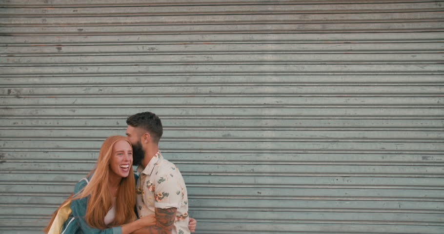 Bearded Hipster guy in front of gate tickling is redhead girl friend in slow motion