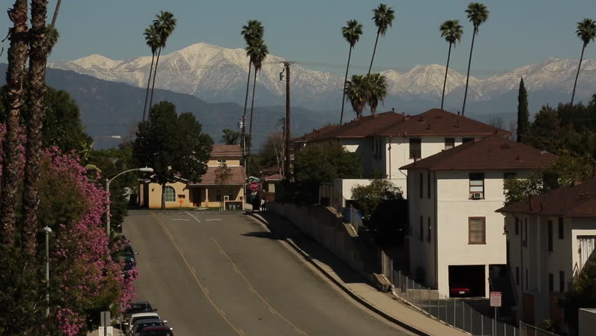 Snow Capped San Gabriel Mountains behind busy streets in Sunny Los Angeles. A Southern California winter scene.  Contrast of Snow and Palm Trees.