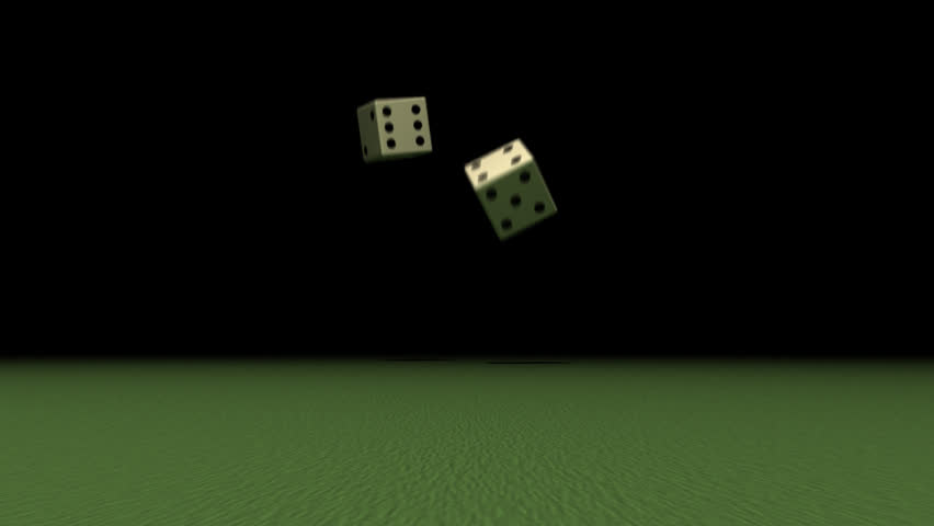 Two black and white dices rolling on green table. The dices are rolling from black background closer to the camera