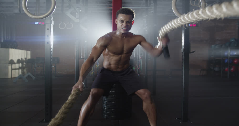 Medium shot slow mo zoom-in, zoom-out young man exercising arms and shoulders with rope in gym | Shutterstock HD Video #9628631