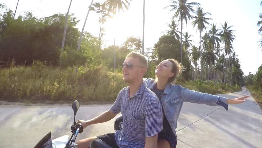 Young Couple Riding Motor Scooter Along Country Road. Slow Motion. HD, 1920x1080.
