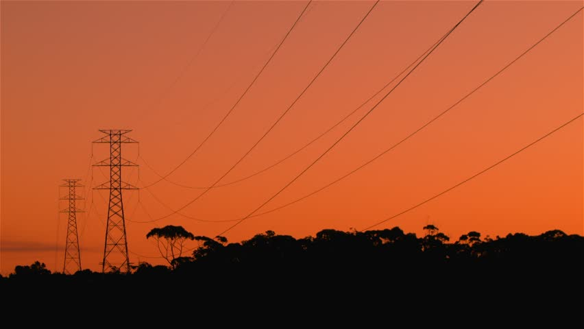 Energy Transmission Power Line Tower Pylon Structures at Sunset.