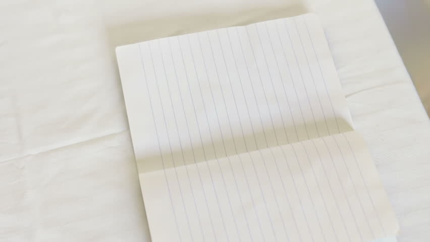 Man hand holding a white pen and writes in a notebook in a line words and phrases.