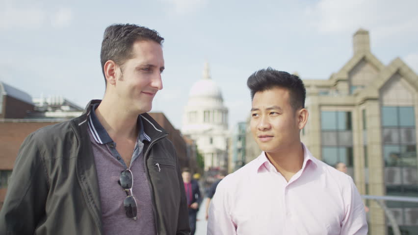 4K Happy casual male friends chatting as they walk through the city - 4K stock footage clip