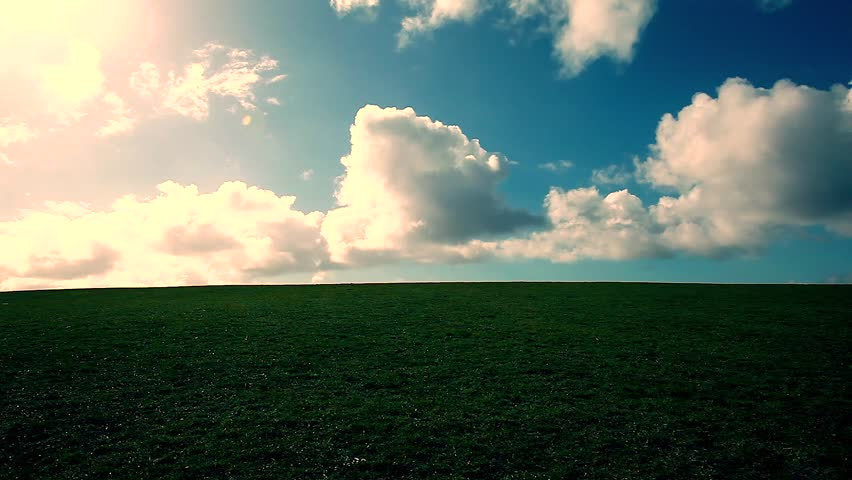 man walking on the edge of a green hill with beautiful clouds above - HD stock video clip