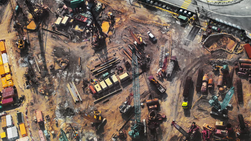 Top view timelapse video of construction site in beginning of building new housing project in Hong Kong. Workers and machinery move fast and busy on development area