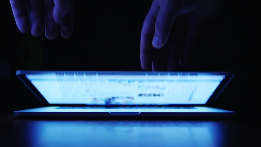 Shutting down the laptop. Men hands close notebook