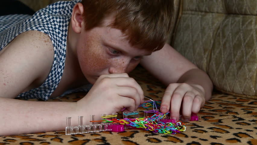 The child spins rubber band loom bracelets on a wooden table background | Shutterstock HD Video #9695546