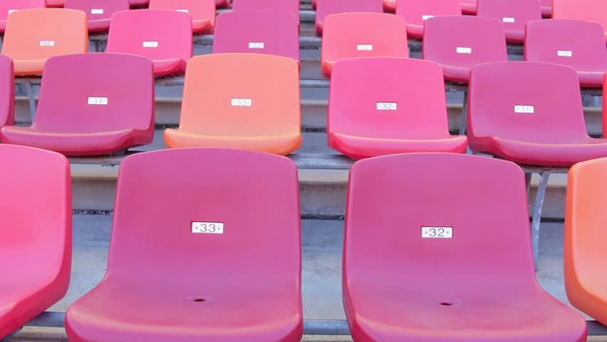 Empty red chairs in a sports stadium in neat rows