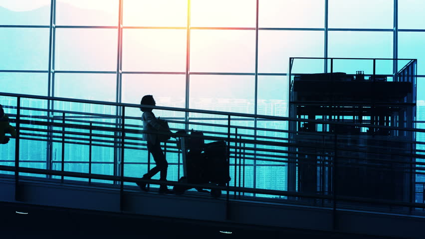 Sunset Silhouettes of Travelers in Airport.