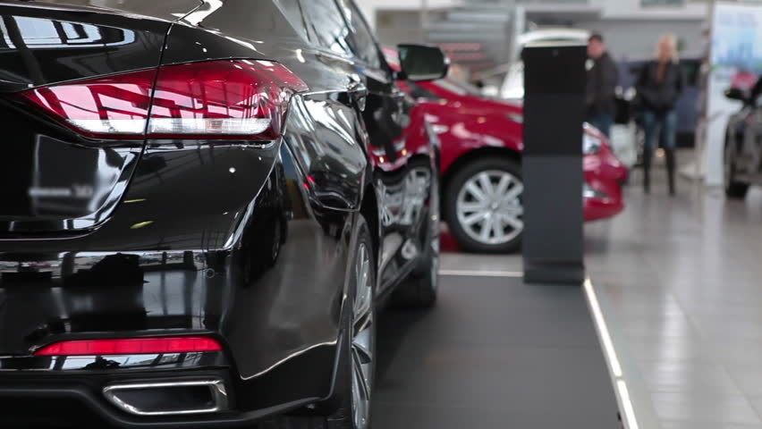 Luxury car dealership showroom with customers and salesmen.
