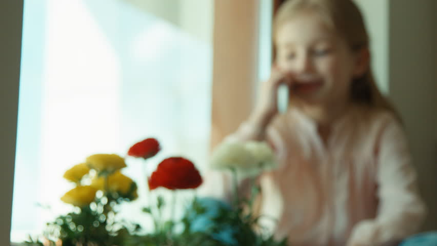 Little girl talking on cell phone sitting on the windowsill. She laughing and looking at camera - 4K stock footage clip